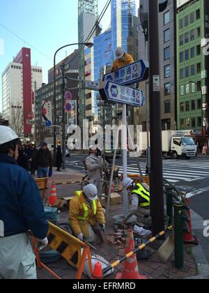 Workers replace Ginza street signs on February 10th, 2015 in Tokyo, Japan. As Japan tries to attract more tourists - Stock Photo