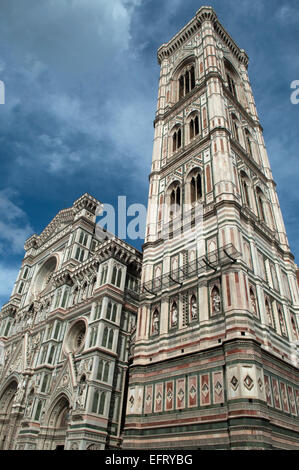 These are marble bell tower and cathedral in Florence, Italy.  Buildings situated against the blue sky background. - Stock Photo
