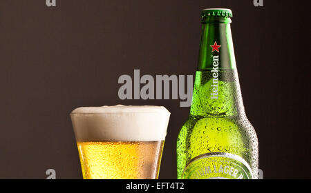 Heineken Lager bottle with glass and frothy head. Both with chilled effect - Stock Photo