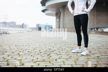 Cropped shot of a young woman standing on urban street while out for a run in the city. Fitness female standing - Stock Photo