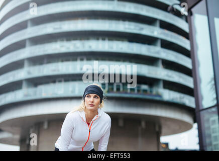 Athlete having a short break from running. Young female exercising on city street. - Stock Photo