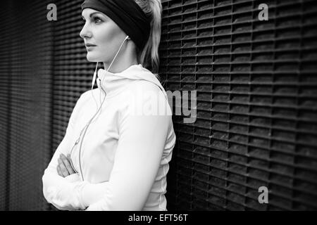 Black and white image of young woman wearing earphones standing leaning a wall looking away confidently. Fitness - Stock Photo