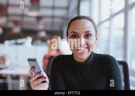Portrait of cheerful young woman holding a mobile phone. African woman looking at camera smiling while at work. - Stock Photo