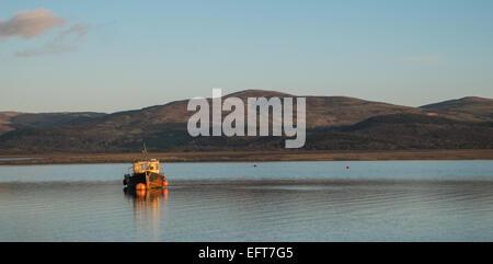 Boat at sunset in Aberdyfi / Aberdovey Estuary on a sunny and calm day. Photo taken from Aberdyfi / Aberdovey village,Mid - Stock Photo