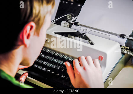 Boy types on an old fashioned mechanical typerighter. - Stock Photo