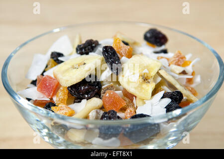 Close up of dried fruit, nut and coconut, or trail mix, in glass bowl - Stock Photo