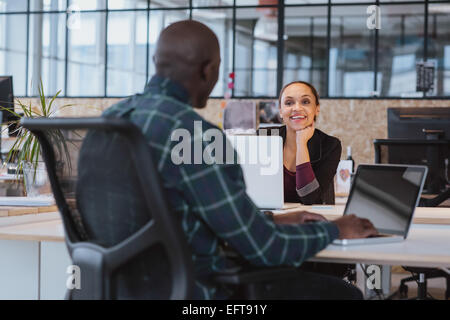 Young african woman sitting at table discussing work with male colleague smiling. Creative people working in office. - Stock Photo