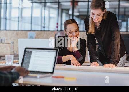 Two young woman at office working on a new creative design. Diverse team of professionals looking at a document - Stock Photo