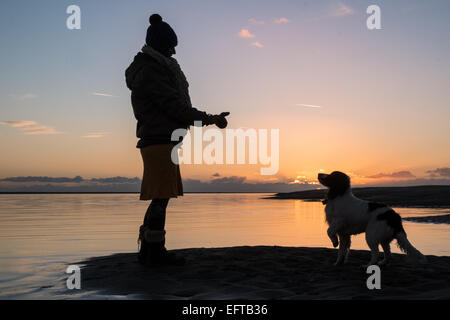 Silhouette of a woman dog walker at sunset in Aberdyfi / Aberdovey village on Dyfi River sunny day,Mid Wales,Gwynedd, - Stock Photo