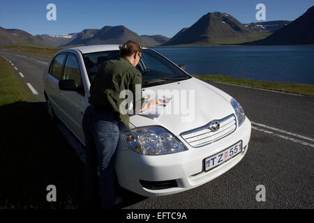 Woman navigating a trip around Dyrafjordur in the Westfjords, Iceland - Stock Photo