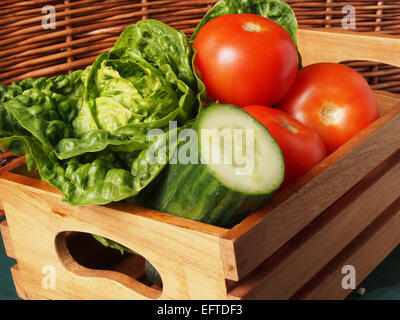 Lettuce tomatoes and cucumber grouped together in a wooden box for storage and transportation - Stock Photo