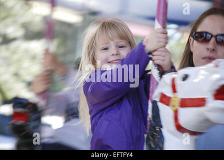 Young child on a merry go round with her mother by her side.  The mother is out of focus as is the background.  - Stock Photo