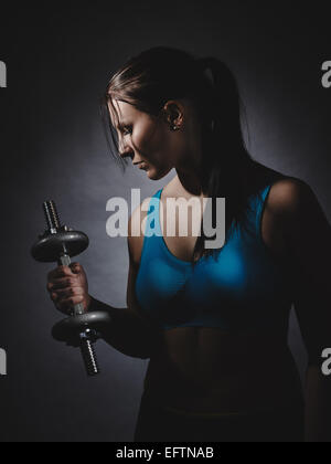 Weightlifting, young woman wearing sportswear and she exercise, studio shot, dark background - Stock Photo