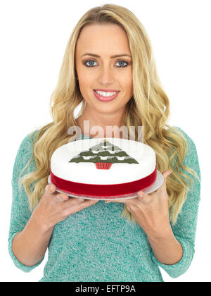 Happy Young Woman Holding A Rich Christmas Fruit Cake Iced And Decorated With A Red Ribbon Isolated Against A White - Stock Photo