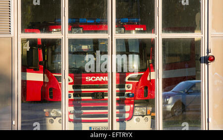 Fire truck behind glass doors at fire station garage - Stock Photo