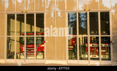Fire trucks behind glass doors at fire station garage , Finland - Stock Photo