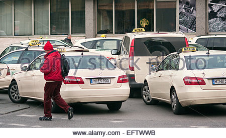 Taxi Rank Outside Main Train Station Man Walking Wearing Red Munich Bavaria Germany - Stock Photo
