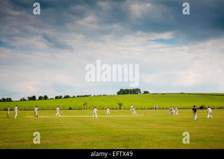 Rural scene with view cricket players playing cricket match on cricket field - Stock Photo