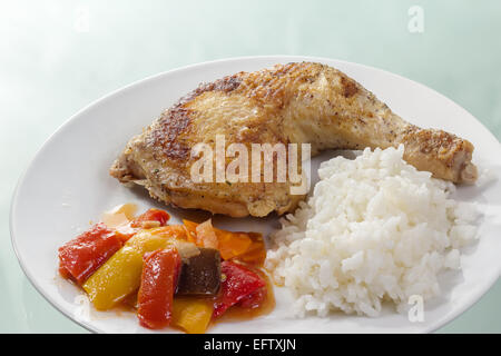 Roast chicken thigh with rice and vegetables on a white plate. - Stock Photo