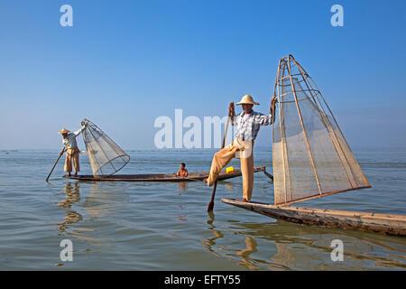 Intha fishermen steering traditional fishing boat by wrapping leg around oar, Inle Lake, Nyaungshwe, Shan State, - Stock Photo