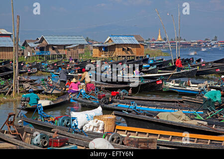 Open boats at lakeside village with traditional wooden houses on stilts in Inle Lake, Nyaungshwe, Shan State, Myanmar - Stock Photo