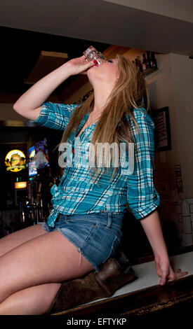 Young Lady, college student chugging an alcohol beverage shot on a bar - Stock Photo