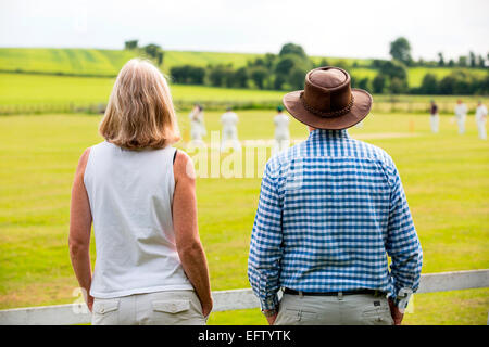Rear view of couple watching cricket match on cricket field - Stock Photo