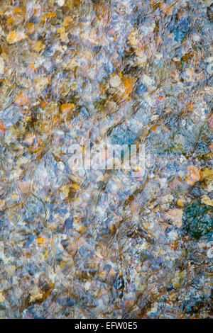 Overhead detail of shallow river water flowing over shingle river bed - Stock Photo