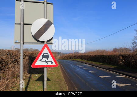 National speed limit applies and slippery road caution sign - Stock Photo
