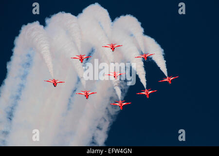The Red Arrows aerobatic display team of Britain's Royal Air Force performing a formation loop during an airshow - Stock Photo