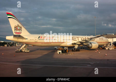Etihad Airways Boeing 777-300ER long haul widebody passenger jet plane parked on the ramp at Manchester Airport, - Stock Photo