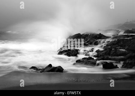 An early morning slow motion images of seawater rushing over sharp, rugged shoreline reef in Laguna Beach, California. - Stock Photo