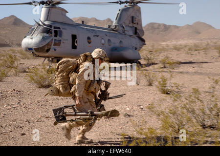 A US Marine carries equipment offloaded from a CH-46 Sea Knight Helicopter during an Integrated Training Exercise - Stock Photo