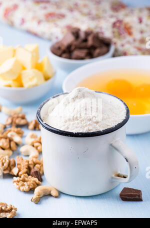 Cup of flour, eggs, butter, nuts and chocolate chunks. Ingredients for baking. Selective focus - Stock Photo