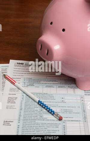 A pink piggy bank along side an American Government Internal revenue service form 1040 (U.S. Individual Income Tax - Stock Photo
