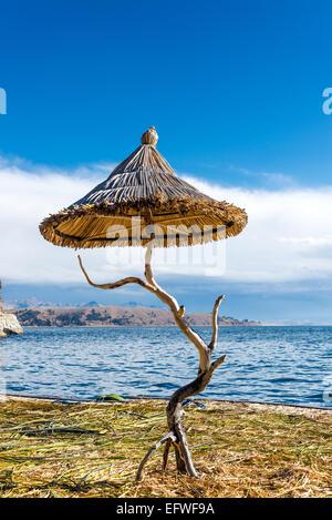 Small reed umbrella on a floating island on Lake Titicaca near Copacabana, Bolivia - Stock Photo