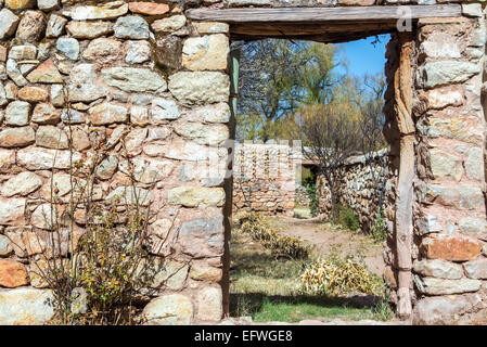 Overgrown courtyard surrounded by stone walls in rural Bolivia - Stock Photo