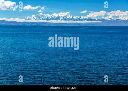 View of the Andes mountains with the deep blue of Lake Titicaca in the foreground - Stock Photo