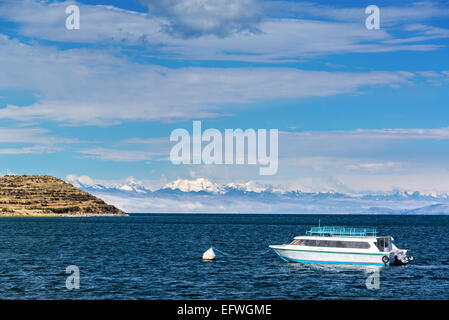 View of a boat on Lake Titicaca with Andes mountains in the background as seen from Isla del Sol in Bolivia - Stock Photo