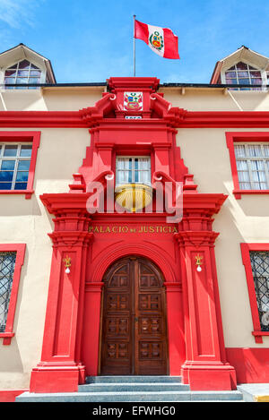 Facade of the courthouse in Puno, Peru with the Peruvian flag flying over it - Stock Photo