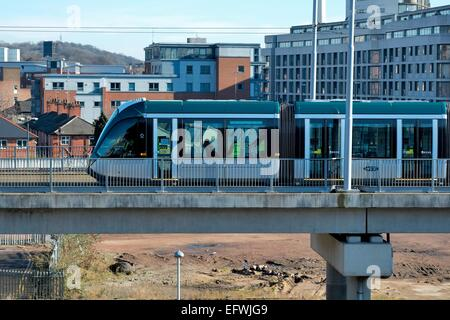 Nottingham express transit tram on a test run heading away from the station street stopping point England UK - Stock Photo
