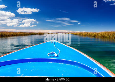 Boat passing through canal with reeds on either side on Lake Titicaca in the region around Uros floating islands - Stock Photo