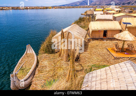 Manmade Uros floating islands and reed boat boat near Puno, Peru on Lake Titicaca - Stock Photo