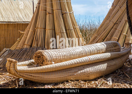 Reed boat on the manmade Uros floating islands on Lake Titicaca near Puno, Peru - Stock Photo
