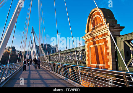 Tourists on the Hungerford Bridge, central London, adjacent to the railway crossing, Charing Cross station in the - Stock Photo