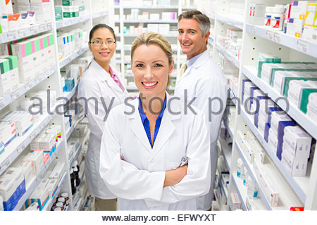 Team of Pharmacists smiling at camera in Pharmacy - Stock Photo