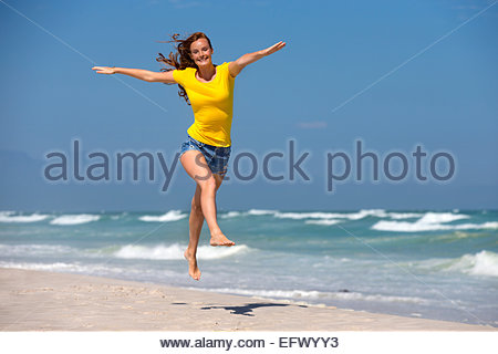 Happy woman, with arms outstretched, leaping in air on sunny beach - Stock Photo
