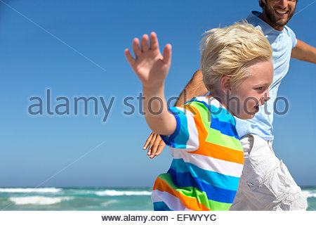 Smiling Father and son, with arms outstretched, running on sunny beach - Stock Photo