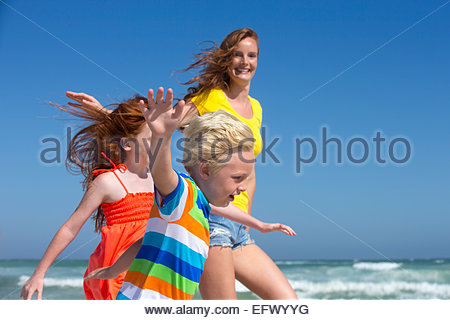 Mother, daughter and son, arms outstretched, running on sunny beach - Stock Photo