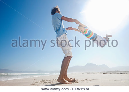 Father swinging son in the air playfully on sunny beach - Stock Photo